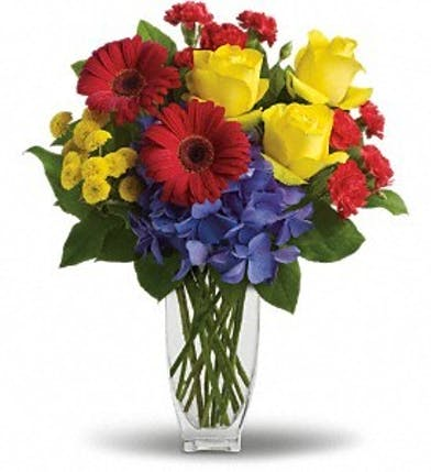 Red, yellow and blue flowers in a clear glass vase.