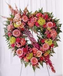 Pastel heart arrangement of assorted flowers presented on an easel.