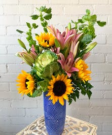 Spring flower arrangement of sunflowers, lilies, bells of Ireland and ornamental kale