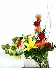 Rectangular glass vase of protea, lilies and roses in a tropical design.