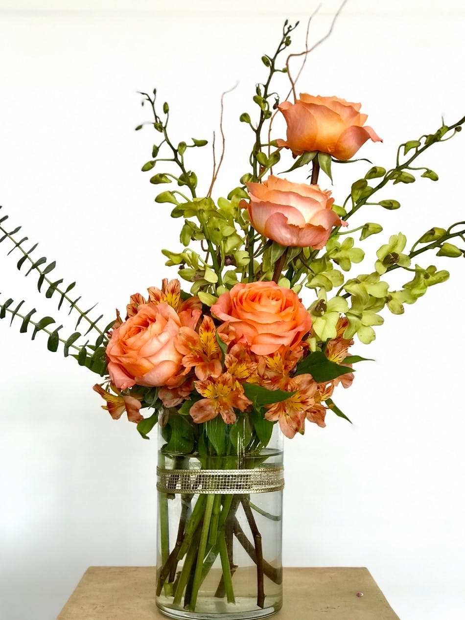Orchids and Peruvian lilies in a clear glass vase.