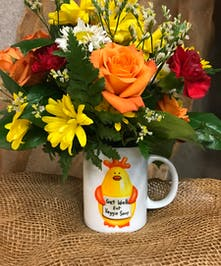 Mug filled with fresh flowers in hues of orange and yellow.