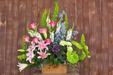Pink, blue, green and purple flowers in a rustic wooden box with greenery.