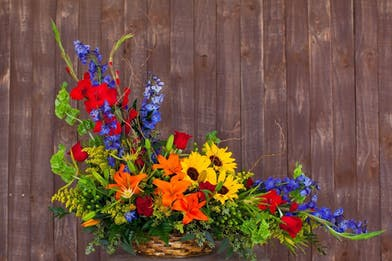 Sunflowers, red gladioli, blue delphinium and roses in a sympathy basket design.