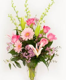 Pink roses, lilies and gerbera daisies in a clear glass vase.