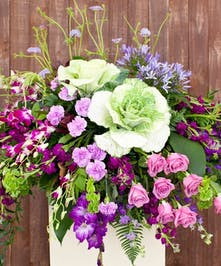 Casket flowers in shades of purple and green.