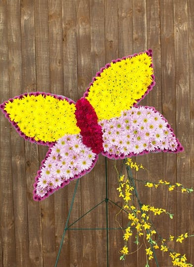 Sympathy tribute of a butterfly created in flowers.