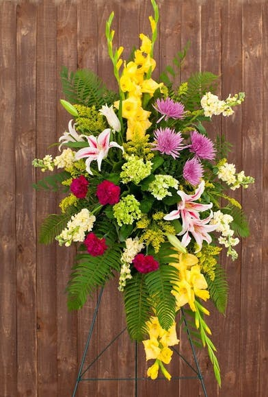 Bright sympathy spray of gladioli, hydrangea, lilies, mums and more.