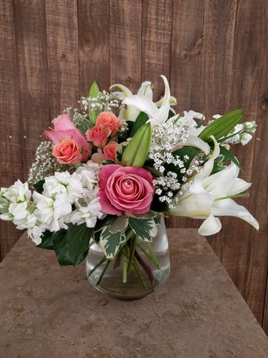 Stock, roses and lilies in a clear glass vase.