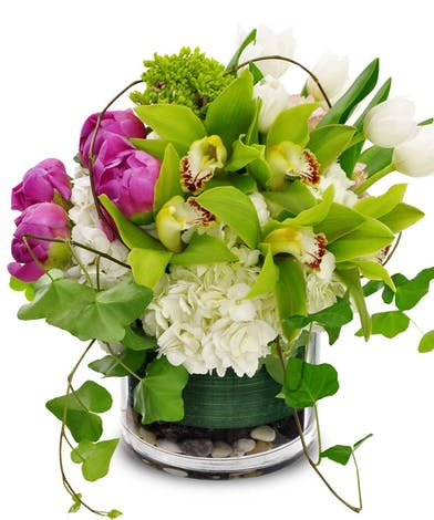 Peonies, orchids, tulips & hydrangea in shades of green, pink and white in a cylinder vase.