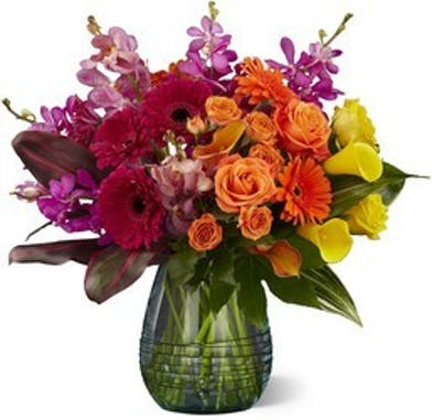 Red, orange, yellow and purple flowers arranged in a clear glass vase.