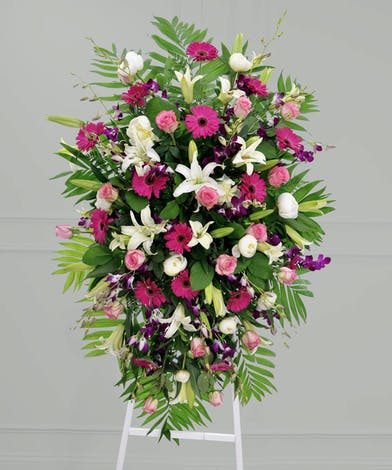 Sympathy spray of white lilies, pink gerbera daisies, pink roses, dendrobium orchids, white peonies and greenery.