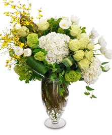 Orchids, tulips, hydrangea and more flowers in shades of green and white in a clear glass vase.