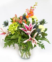 Peach lilies, hydrangea and other flowers in a clear glass vase.