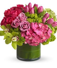 Pink and green flowers in a leaf-lined cylinder vase.