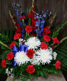 Patriotic sympathy arrangement of red, white and blue flowers accented with ribbon.