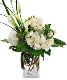White hydrangeas, white calla lilies and beautiful greens in a rectangular glass vase.