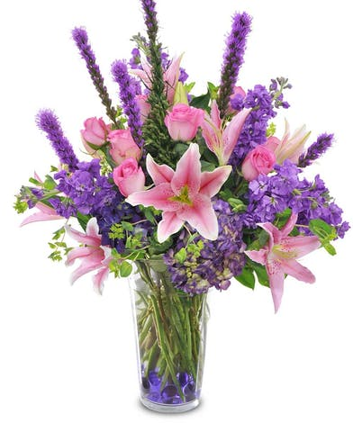 Purple and pink flowers in a glass vase with purple gems at the bottom.
