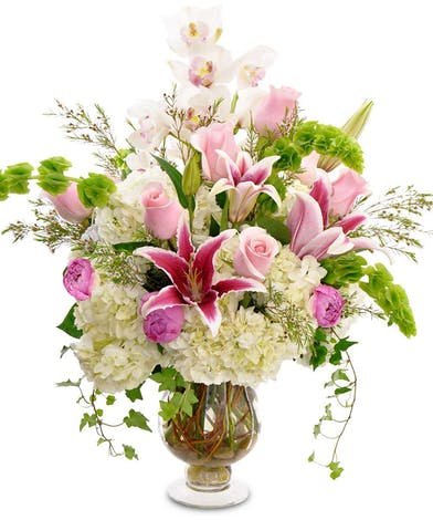 Orchids, roses, peonies, stargazer lilies, hydrangeas and greenery in a clear glass vase.