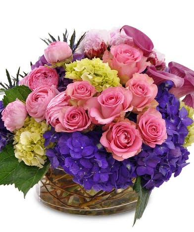 Pink and purple flowers in a glass vase.