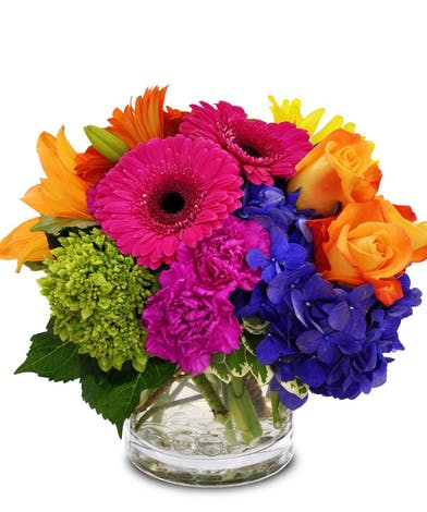 Orange, purple, blue, green and magenta flowers in a clear glass vase.