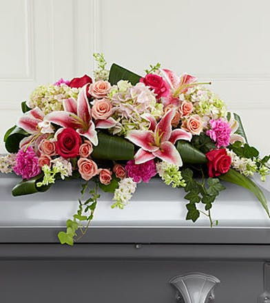 Mixed flower casket spray in shades of pink.