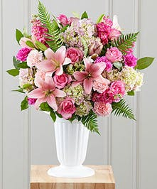 Tall white vase filled with pink roses, hydrangea, carnations, stock and Asiatic lilies.