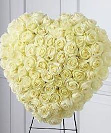 Elegant all-white heart tribute of roses presented on an easel.