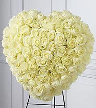 Elegant all-white heart tribute of roses presented on an easel.