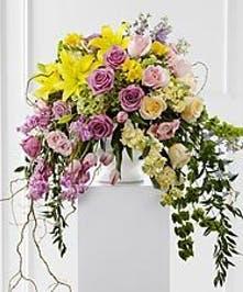 Lavender and yellow flowers, greenery and curly willow in a white sympathy urn.