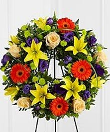 Sympathy wreath of creme roses with purple, orange and green flowers.
