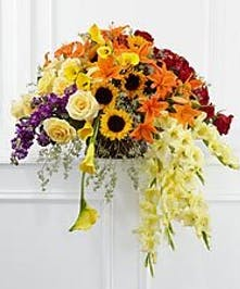 Cream and red roses, purple stock, yellow mini calla lilies, orange Asiatic lilies, yellow gladiolus, sunflowers and lush greens.