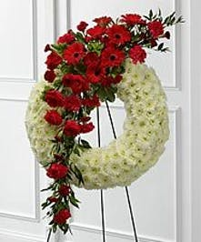 White wreath arrangement accented with burgundy mini carnations and greenery.