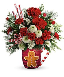 Gingerbread man mug filled with holiday flowers and winter greenery