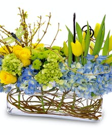 Blue and yellow flowers in a long glass cube vase.