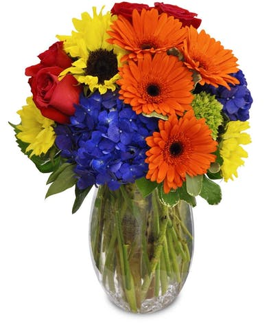 Orange, blue, coral and yellow flowers in a clear glass vase.