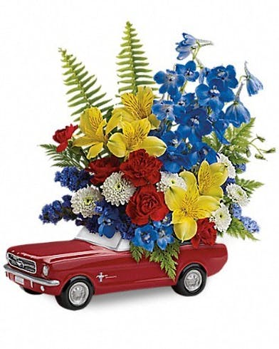MIniature Ford Mustang container filled with blue, yellow and red flowers and greenery.