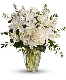 All-white bouquet of sympathy flowers in a glass vase.