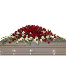 Red and white casket spray accented with greenery.