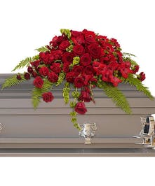 Casket spray of red roses, gerberas, gladioli and carnations.