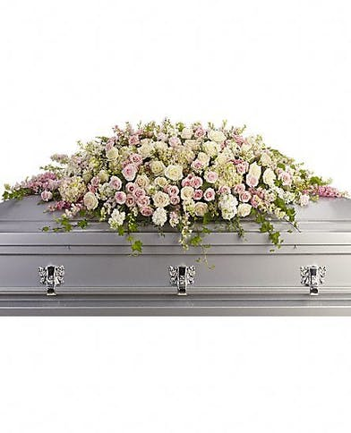 Casket spray of soft pink, white and creme blooms.