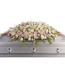 Feminime casket spray of pink hydrangea, roses and larkspur with white roses, stock and waxflower.