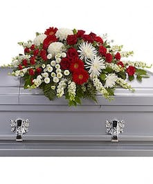 Traditional funeral spray of white and red flowers with greenery.