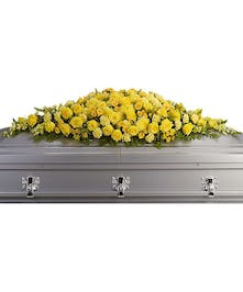 Yellow casket spray of roses, carnations, chrysanthemums, snapdragons and more.