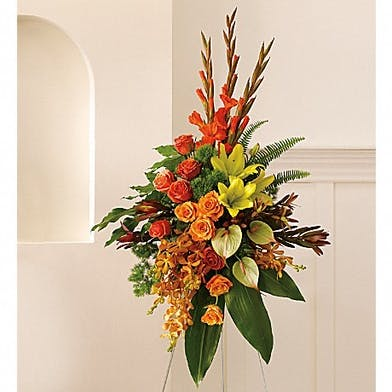 Tropical sympathy spray of anthuriums, roses and tropical greenery.