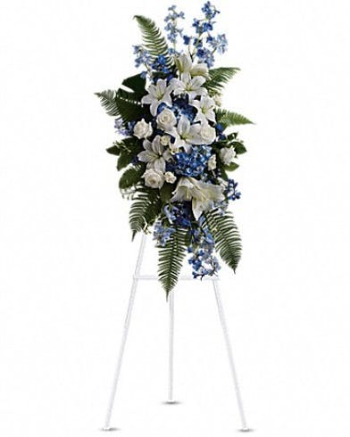 Sympathy spray of blue and white flowers presented on an easel.