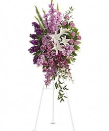 Lavender, purple and white sympathy spray accented with greenery.