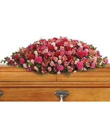 Pink casket spray with alstroemeria, carnations and greenery.