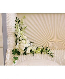 White arrangement of roses, sray roses and more for a casket corner.