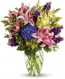 Pink lilies, blue hydrangea, and other flowers in a clear glass vase.